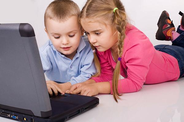 Мальчик и девочка играют в ноутбук