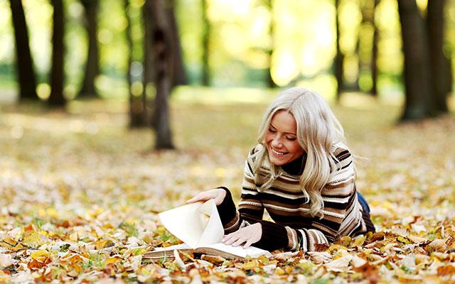 Девушка читает книгу, лёжа на земле с опавшей осенней листвой