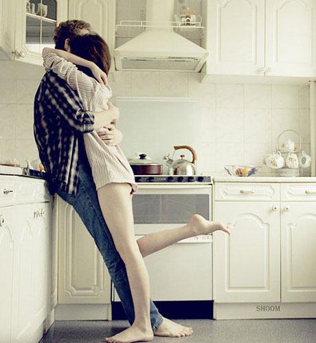 Влюблённая парочка обнимается на кухне